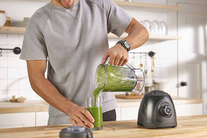 Horizontal image of a man pouring a green smoothie into a glass in a kitchen.