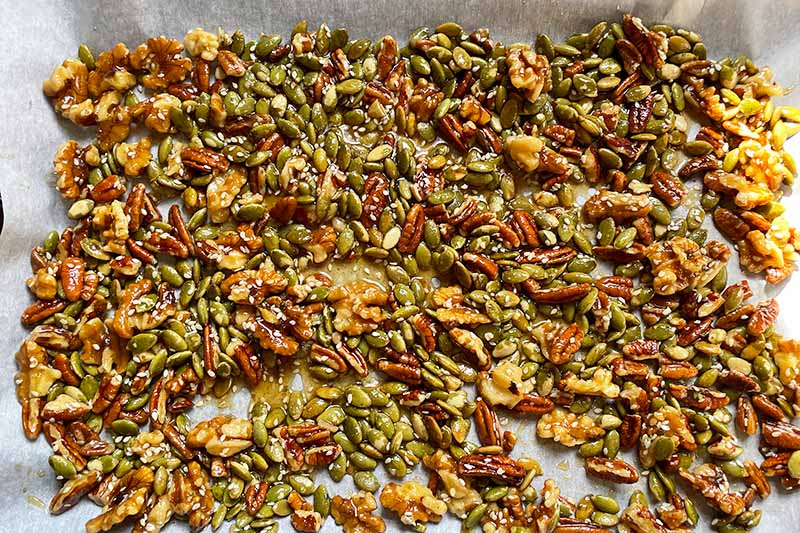 Horizontal image of a wet mixture with nuts and seeds spread on a baking sheet lined with parchment paper.
