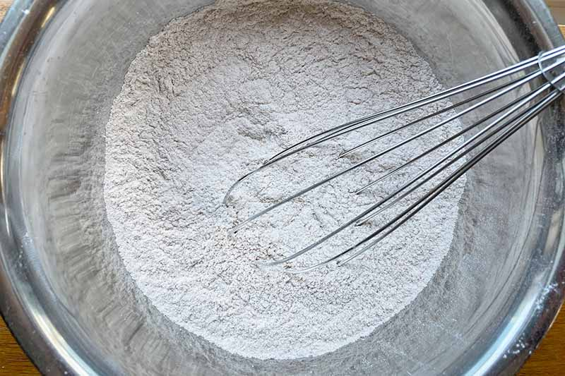 Horizontal image of flour in a bowl with a whisk.