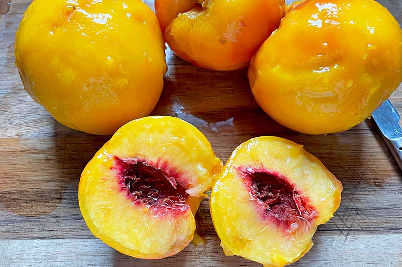 Horizontal image of peeled and halved boiled peaches on a wooden surface.