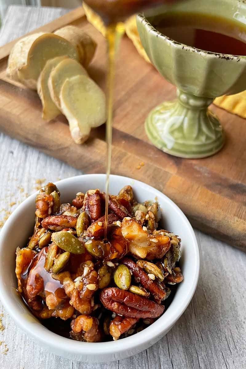 Vertical image of pouring maple syrup over a bowl of toasted walnuts and pecans in front of a cutting board with sliced ginger.