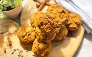 Horizontal image of a pile of pumpkin muffins on a wooden cutting board next to a towel, cinnamon sticks, and a vase with plants.