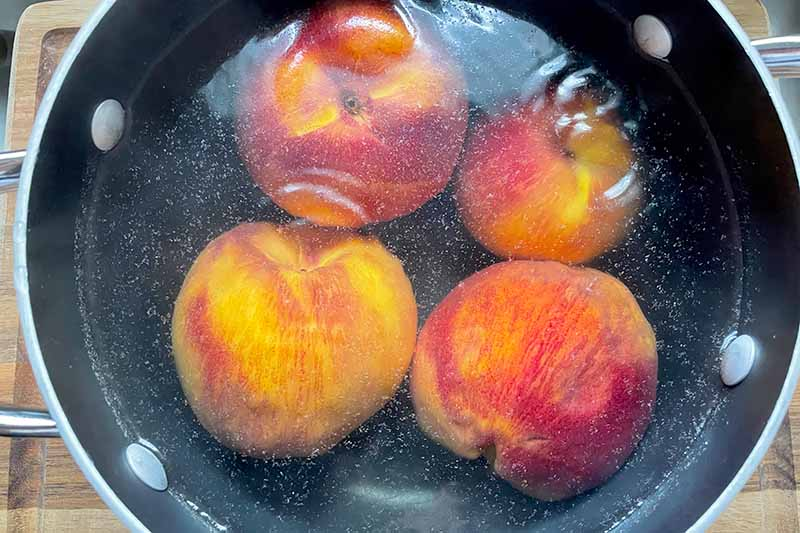 Horizontal image of boiling whole fruit in a pot with water.