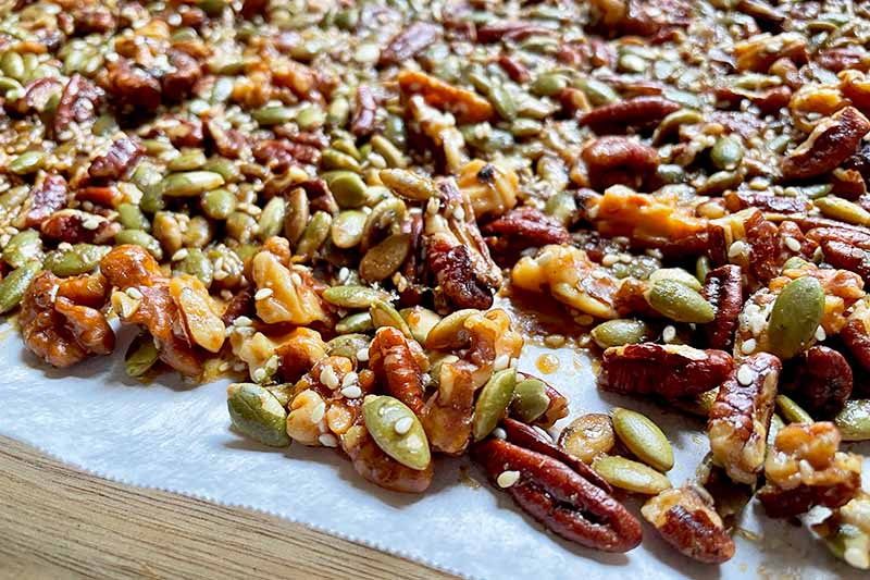 Horizontal image of a toasted mixture of pecans, walnuts, and seeds on a baking sheet lined with parchment paper.