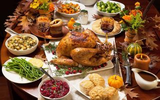 Horizontal image of a large Thanksgiving table with assorted food.