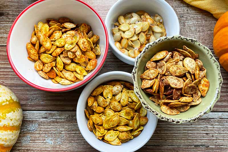 Horizontal image of four bowls filled with assorted spiced pumpkin seeds on a wooden surface.
