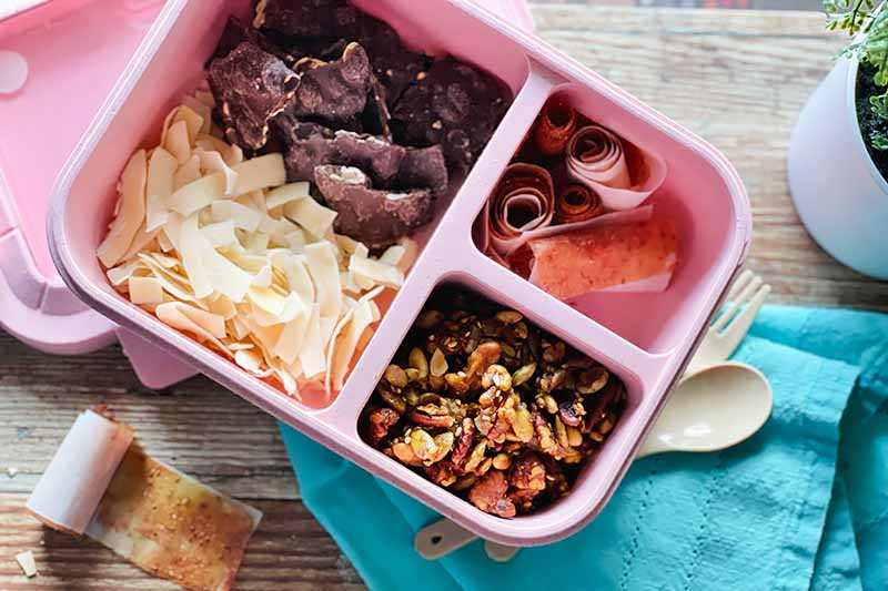 Horizontal image of a pink container with compartments filled with assorted food next to a blue towel.