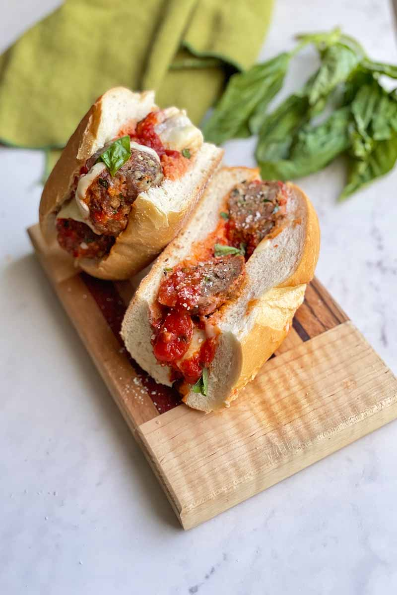 Vertical image of a hoagie with cooked small mounds of ground beef with tomato sauce and melted cheese on a wooden cutting board next to herbs and a green towel.