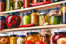 Horizontal image of wooden shelves full of assorted jarred vegetables and sauces.