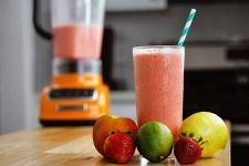 An orange blender filled halfway with a pink mixture is in soft focus on a wood kitchen island in the background, with a tall glass filled to the top with the beverage in the foreground, with a blue and white striped straw in the drink, surrounded by a fresh peach, two strawberries, a lime, and a lemon.