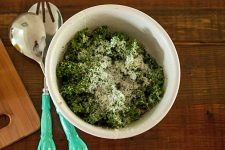 A Simple Kale Salad with Garlic, Lemon, and Pecorino. Top down view of a white bowl on a dark wooden background.