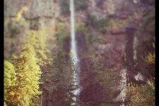 An image showing a faraway waterfall on the side of a high mountain.