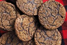 Five dark chocolate cookies are arranged on black and white plaid flannel, overlapping at the edges.