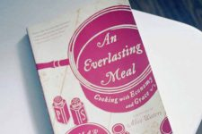 A copy of the An Everlasting Meal Cookbook on a white table.