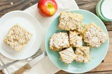 Overhead shot of a white plate topped with a slice of vegan apple cake to the left and a larger light green plate with more pieces of the baked good to the right, with a green glass of almond milk, an apple, a serrated knife with a wood handle, and a fork on an unfinished wood background.
