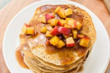 Close up of stack of apple cinnamon pancakes on white plate. Oblique view.