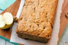 Closeup closely cropped image of a loaf-shaped breakfast cake, on a rectangular piece of parchment on a slightly larger brown wood board, on a pastel aqua-colored cloth on top of a white wood surface, with half an an apple to the left that is cut side up.