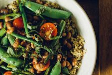 Horizontal image of a dish with asparagus, tomatoes, and snap peas.