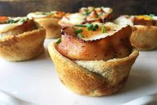 Horizontal image of baked toast cups with bacon and eggs and chive garnish.