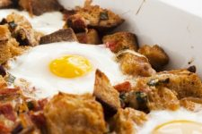 A close up image of a delicious breakfast bake with eggs on top.