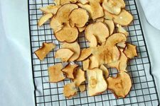 Baked Apple Chips cooling on a wire rack, on a white table.