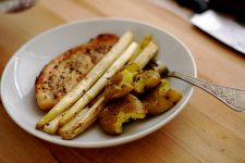 A plate of baked tilapia with white asparagus and baby potatoes.