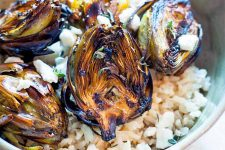 Closeup of grilled baby artichokes on a bed of brown rice with crumbled feta and fresh thyme.