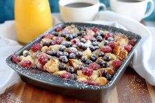 Horizontal image of a metal baking pan of cubed bread baked with beaten egg and fresh fruit, sprinkled with confectioner