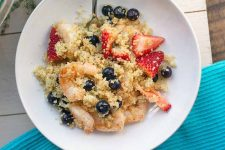 Overhead horizontal image of a shallow white ceramic bowl of quinoa with spices, honey, shrimp, blueberries, and sliced strawberries, on an off-white table covered partway with a blue place mat.