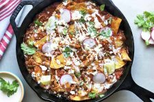 Horizontal top-down image of a black cast iron skillet filled with a chicken and sauce nacho dish topped with fresh garnishes and crema.