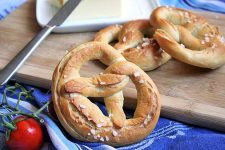A close up of a traditional German lye pretzel centered in the frame with a cutting board and a stick of butter in the background. A red cherry tomato sits to the lower left.