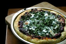 Large spinach pizza on top of wooden board.