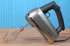 The Breville BHM800SIL Hand Mixer Review on a maple butcher block table with a blue painted wooden wall behind it.