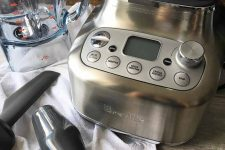 Horizontal image of a close-up view of the Breville control panel, tamper, and scoop, with the jug in the background.