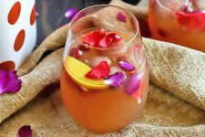 Horizontal image of one cocktail with colorful garnishes on a burlap towel.
