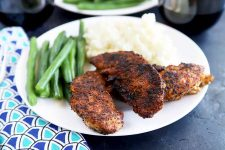 Horizontal image of a white plate with blackened tenders next to green beans and mashed potatoes.