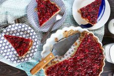 Top-down shot of a cranberry tart in a white pie plate with wood and metal server, with three servings on small black and white dessert plates.