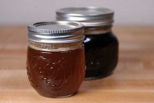 Two jars of brown butter sitting on wooden table | Foodal