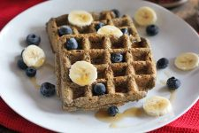 Two buckwheat buttermilk waffles on a plate with sliced banana and fresh blueberries on top, on a red cloth background.