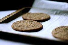 Image of buckwheat ginger cookies on top of a parchment paper on a tray.