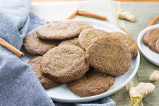 Horizontal image of a white ceramic plate of homemade gluten-free buckwheat ginger cookies, on a gray surface with scattered whole cinnamon sticks, a folded pale blue cloth, fresh ginger, and another smaller plate of the same dessert to the right of the frame.