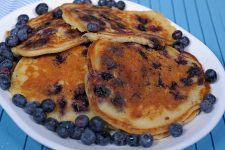 A white oblong platter with 8 giant blueberry buttermilk pancakes filling the plate | Foodal