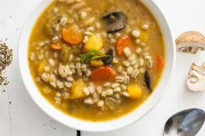 Top down close up view of a butternut and barley winter soup recipe in a white, ceramic bowl.