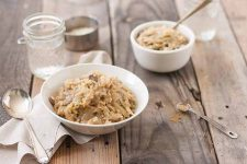 Oblique photo of two bowls of cabbage mushroom risotto on a rustic, wooden table top.