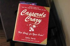 Book with red cover called Casserole Crazy, on a brown table.
