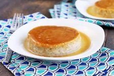 A white plate of Mexican flan with coconut sauce is at the center of the frame with another to the top right, on folded dark and light blue patterned cloth napkins with a fork, on a brown wood surface.
