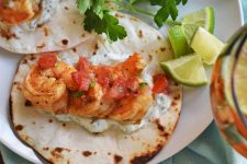 Overhead horizontal image of two shrimp tacos on a plate, with crema and pico de gallo, with a sprig of fresh cilantro and lime wedges, and a cocktail to the right of the frame.