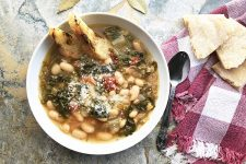Horizontal image of a bowl of soup with cannellini and escarole on a red checkered towel.