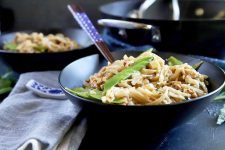 Horizontal image of two black bowls with chicken chow mein on a black surface with a gray napkin and chopsticks.