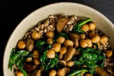 Horizontal image of a grain bowl topped with beans and vegetables.